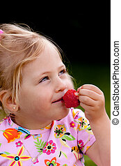 Child eating a strawberry in the garden