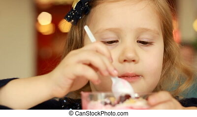 Child eating a sweet dessert in a cafe. Closeup portrait -...