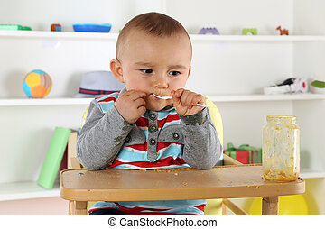 Child eating baby food porridge with spoon