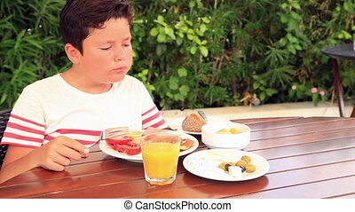 Child eating breakfast at the garde - Young boy eating...