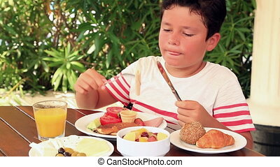 Child eating breakfast at the garden - Young boy eating...