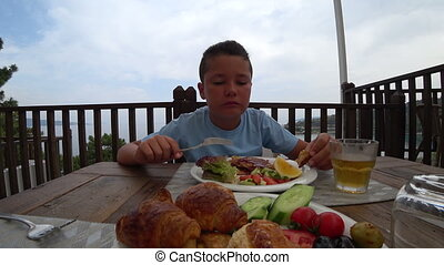 Child eating breakfast at the outdoor - Young boy having...