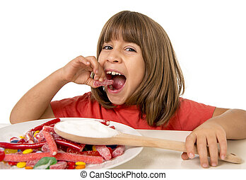 child eating candy like crazy in sugar abuse and unhealthy sweet nutrition concept