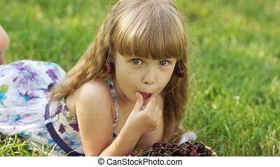 Child eating cherries lying on the