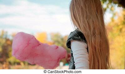 Child eating cotton candy at amusement park