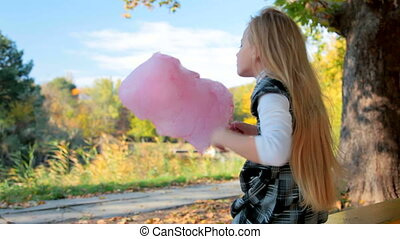 Child eating cotton candy in a park