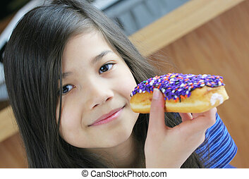 Girl eating colorful topped stuffed donut.
