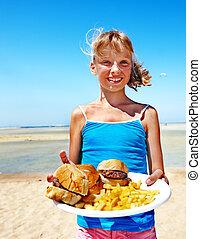 Child eating fast food. - Child eating fast food at beach...