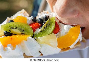 Child eating fresh waffle cake with fruit and whipped cream.
