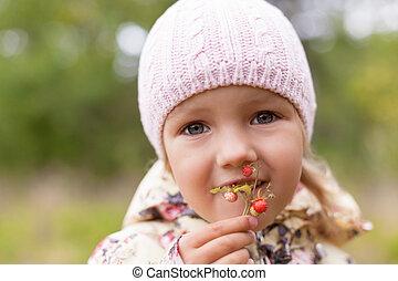 child eating fun wild strawberry twig holding hand shallow DOF