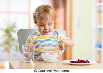 child eating healthy food with a spoon