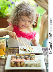 Child eating sushi in bar