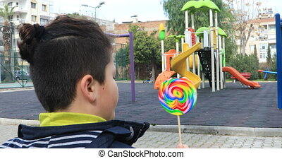 child eating lollipop at the playground