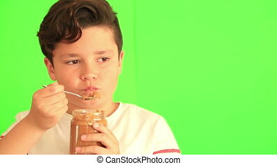 Child eating peanut butter against chroma key green screen...