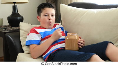Child eating peanut butter - Portrait Of A Child Sitting On...