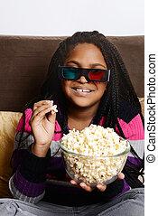 child eating popcorn watching movie
