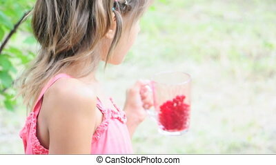 child eating red current