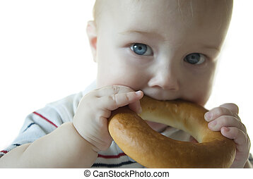 Child eats a bagel - Blue-eyed child eats drying and looks...