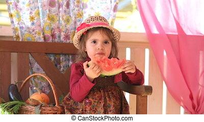 child eats a tasty water-melon, sitting on a summer verandah