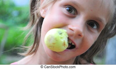 Child eats an apple outdoor
