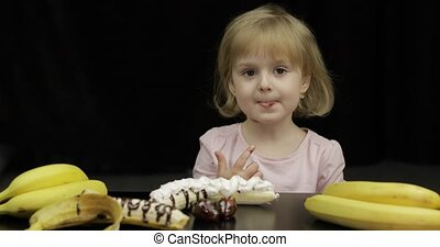 Child eats banana, strawberry with melted chocolate and whipped cream