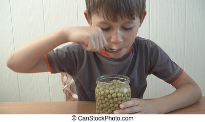 child eats green peas