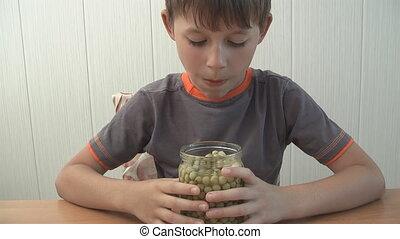 child eats green peas