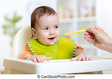 Child eats healthy food sitting in hich chair in kitchen