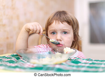 child eats with spoon