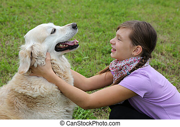 Child embracing dog on a meadow