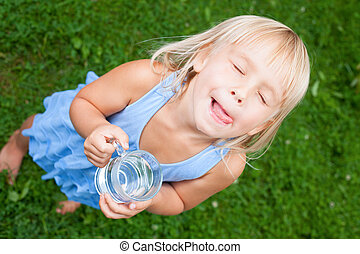 Child enjoy drinking water outdoors - High angle view shot...