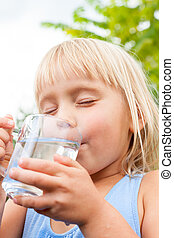 Child enjoy drinking water outdoors - Blonde little girl...
