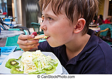 child enjoys ice cream sitting outdoors