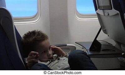 Child entertaining with mobile phone in the plane