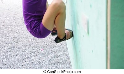 Child exercising on rock climbing b