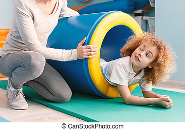 Child exercising with play tunnel during sensory therapy