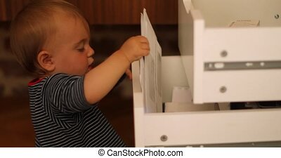 Child exploring open drawers - Side view of curious baby boy...