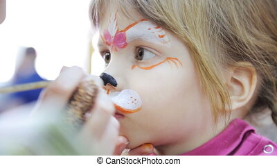 Child face painting like a cat