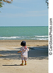 child facing the sea on a summer day