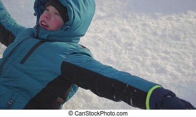 Child falls into the snow in slow motion. Active sports outdoors. Winter Sunny day