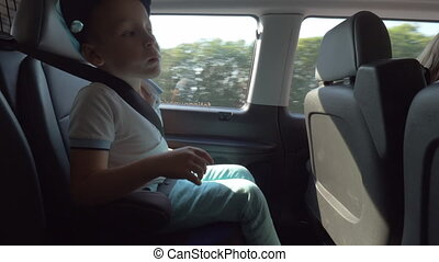 Child fastened with safety belt traveling by car