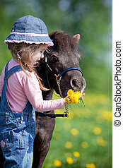 Child feeding a small horse in spring.
