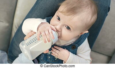 Child Feeding - High angle view of cute baby girl lying in...