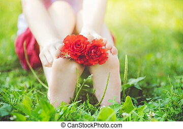 Child feet with red rose on green grass