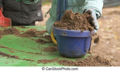 Child filling bucket with sand on table in sandbox -...