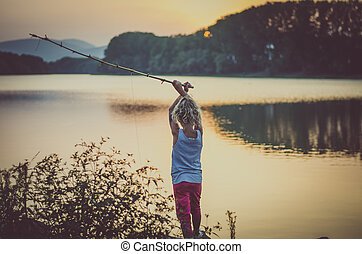 child fishing on the lake at sunset time