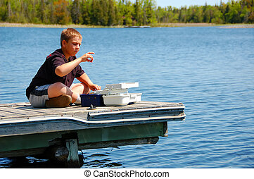 Child Fishing - Child selecting the right bait sitting on a...