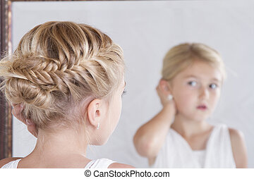 Child fixing her hair while looking in the mirror. - Child...