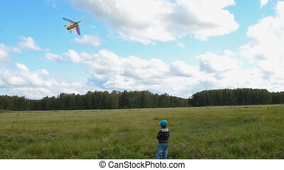 Child flying kite in the countryside