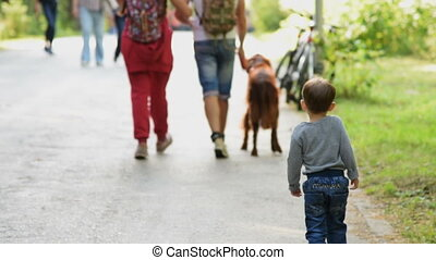 Child following the couple with dog